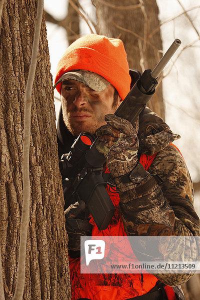 Whitetail Deer Hunter Waits Behind Tree
