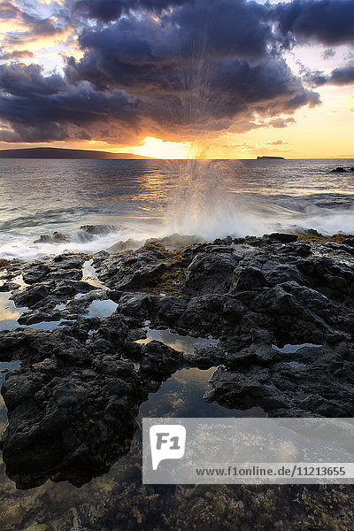 'Water splashing onto the lava rock along the coast at sunset; Hawaii,  United States of America'