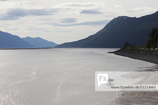 A man paddle-boards out in Turnagain Arm in Southcentral Alaska.