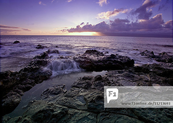 'Water splashing on the black lava rock on the shore as the sun sets over the horizon; Hawaii  United States of America'