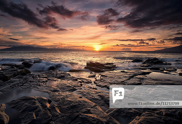 'Sunset over the ocean with wet black rock along the shore; Hawaii  United States of America'