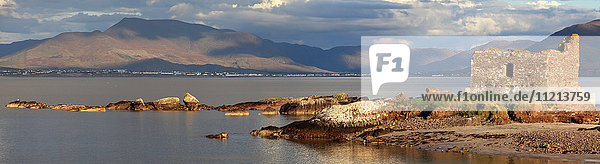'Ruins of a building at the water's edge with mountains in the distance; Portmagee  County Kerry  Ireland'
