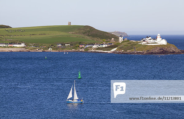 'Sailboat in a harbour with Roche's Point Lighthouse along the coastline  Roches Point; County Cork  Ireland '