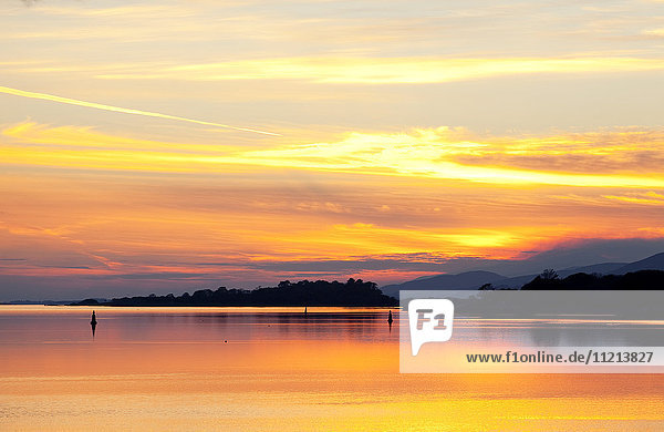 'A dramatic and colourful sunset reflected in water with silhouetted shoreline and mountains; Kenmore  County Kerry  Ireland'