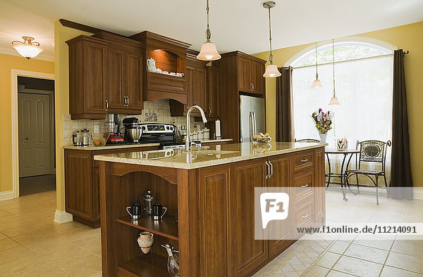 'Kitchen room with island inside a cottage style residential home; Quebec  Canada'