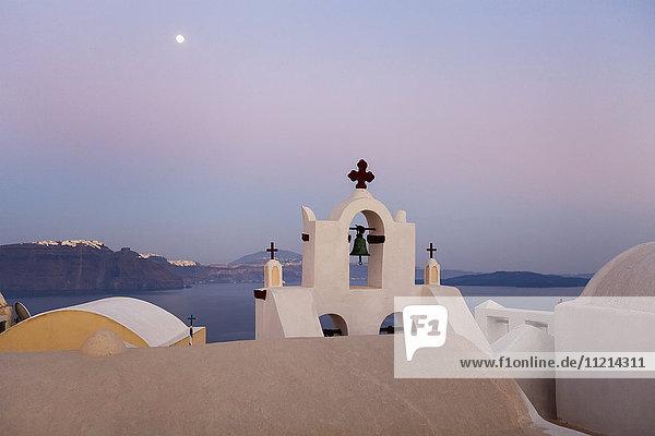 'Orthodox church with bell and a moon high in the sky at dusk; Oia  Santorini  Greece'