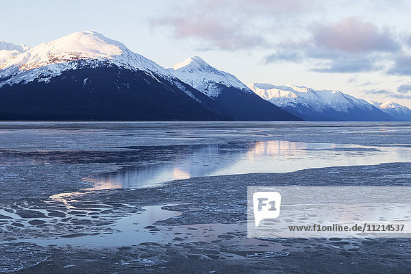 'Ice on the water of Turnagain Arm  with snow capped mountains reflected in the water  south of Girdwood; Alaska  United States of America'