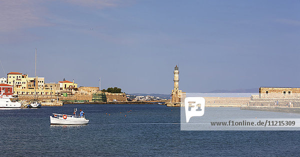 The lighthouse and historic Venetian harbour with boat in Chania old Town  Crete