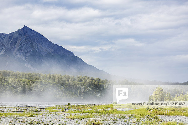 'River silt being blown about Matanuska River bed on a windy and cloudy day  King Mountain in the background  south-central Alaska in summertime; Palmer  Alaska  United States of America'