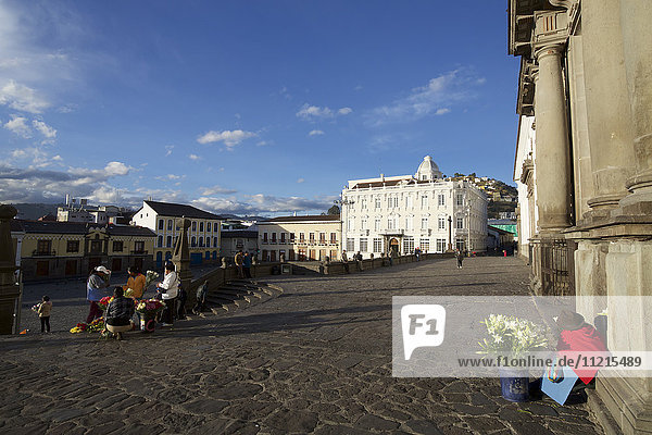 View of square with colonial buildings and flower seller outside Monasterio St Francis