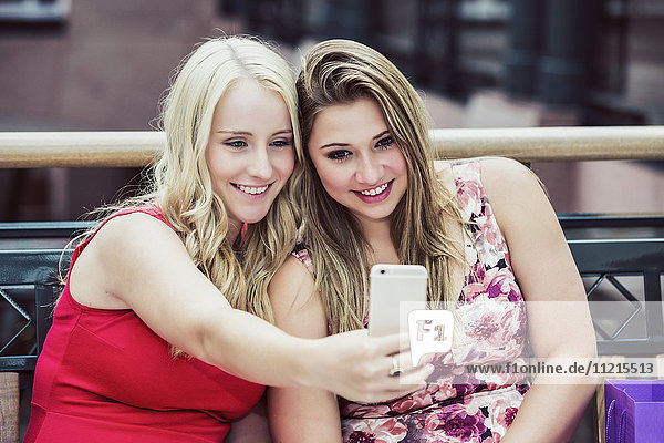 'Two beautiful young women taking a break to take a selfie while out shopping together in an indoor mall; Edmonton  Alberta  Canada'