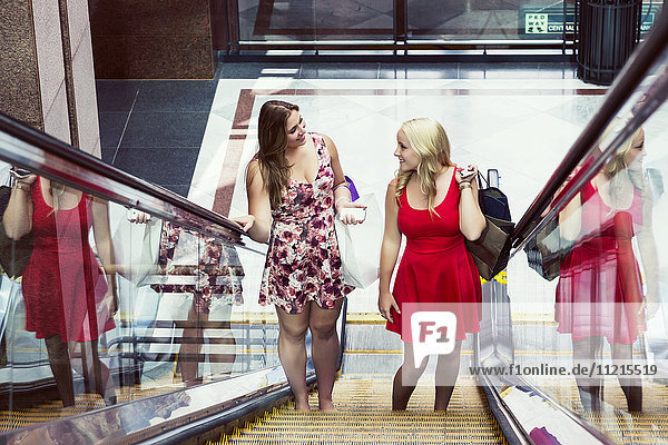 'Two beautiful young women in dresses out shopping together and riding an escalator in an indoor mall complex; Edmonton  Alberta  Canada'