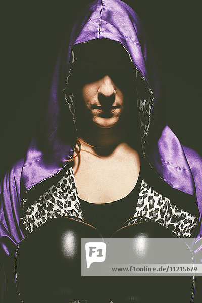 'A woman with a purple satin hooded cape over her head  an animal print shirt and black boxing gloves; Saskatchewan  Canada'