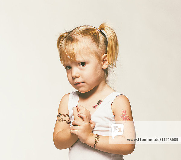 'Portrait of a young girl with pigtails and numerous tattoos on her arms against a white background; Saskatchewan  Canada'