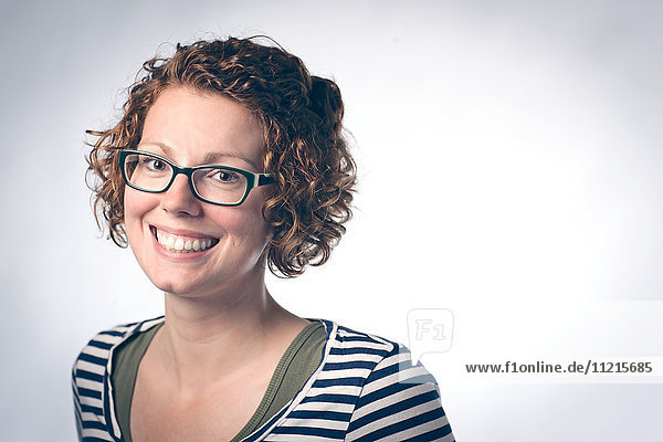 'Portrait of a young woman with curly red hair and eyeglasses against a white background; Regina  Saskatchewan  Canada'