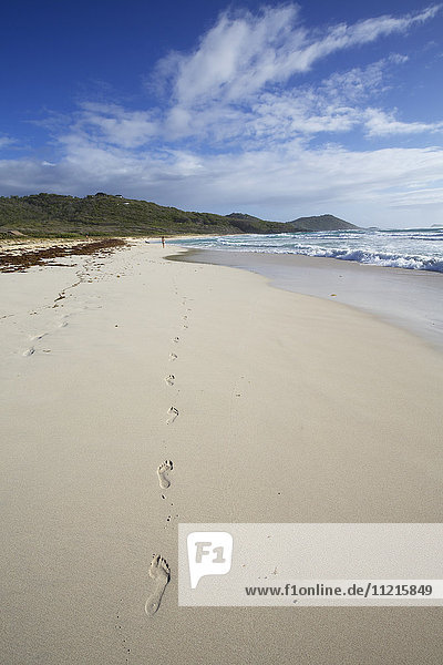 Footprints in white sand beach with sea surf