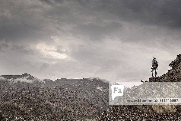 'Hiker standing at the top of a mountain looking out  just north of Tupiza; Bolivia'