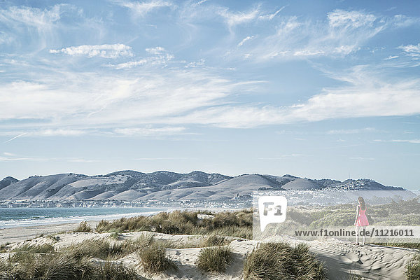 'Woman standing on sand dune overlooking ocean; San Luis Obispo  California  United States of America'