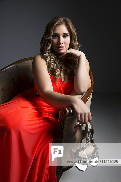 'A beautiful young woman sitting in a chair wearing an orange dress and posing for the camera in a darkly lit studio with white background; Edmonton  Alberta  Canada'