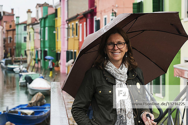'A woman stands beside a canal with an umbrella with colourful houses in a row in the background; Venice  Italy'