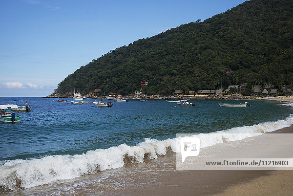 Waves breaking along the beach with boats in the water just off the shore; Yalepa  Jalisco  Mexico