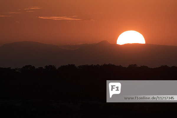 'Setting sun overtop of the African landscape; South Africa'