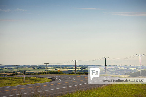 'Electrical wires along a curving road with farmland in the distance; Saskatchewan  Canada'