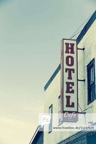 'Hotel sign on the side of a building against a blue sky; Saskatchewan  Canada'