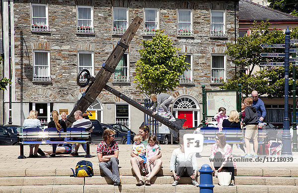People sitting on steps and benches in town with a large anchor on display; Bantry  County Cork  Ireland