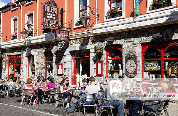 Customers sitting on an outdoor patio of a restaurant along a street; Kenmare  County Kerry  Ireland