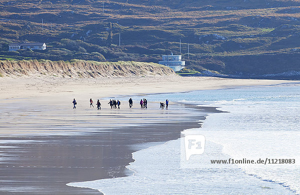 A group of people walking on the beach; Derrynane  County Kerry  Ireland