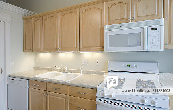 Empty kitchen with light colored cabinets
