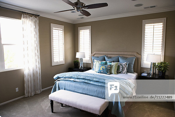 Collection of throw pillows on bed in bedroom  Tustin  California  USA