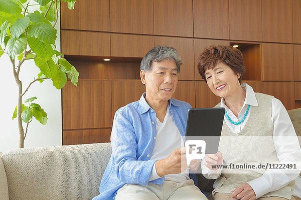 Fashionable Japanese senior couple with tablet on sofa