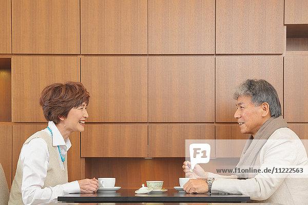 Fashionable Japanese senior couple enjoying a cup of coffee