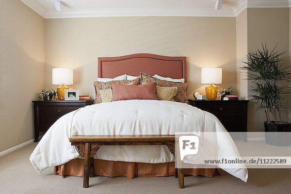 Arranged pillows on tidy bed with lit table lamps in the bedroom at home