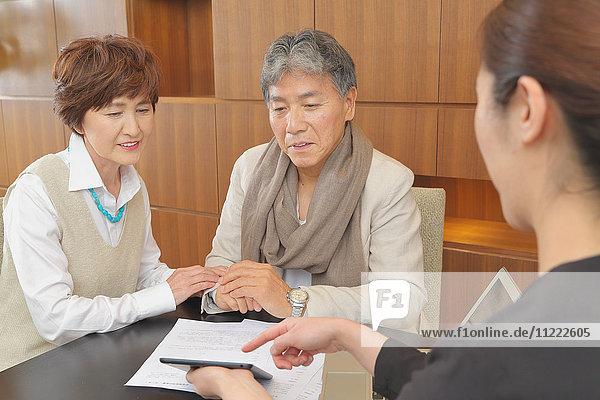 Fashionable Japanese senior couple discussing with advisor