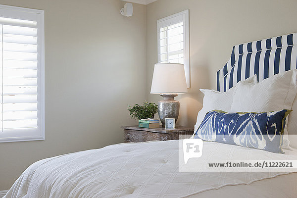 Arranged pillows on tidy bed with lit table lamp in the bedroom at home