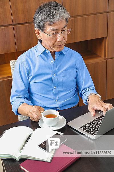 Fashionable Japanese senior man working