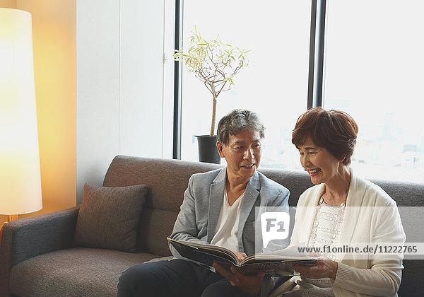 Fashionable Japanese senior couple on the sofa