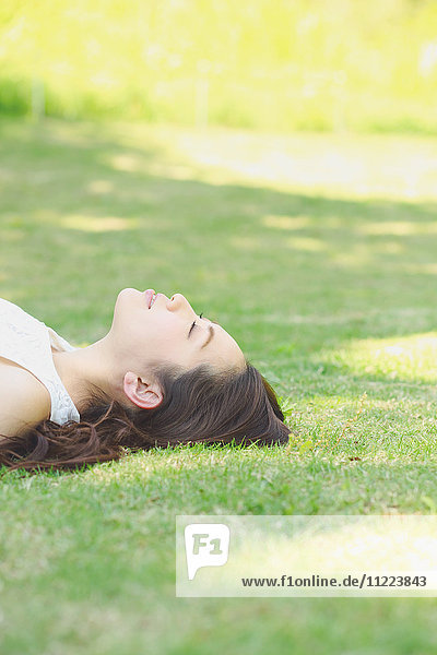 Portrait of young Japanese woman laying on green grass
