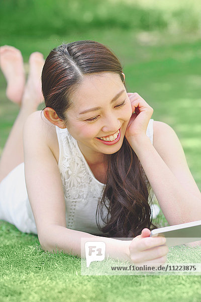 Portrait of young Japanese woman laying on grass with smartphone