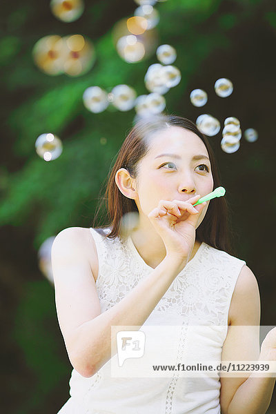 Young Japanese woman blowing soap bubbles in a city park
