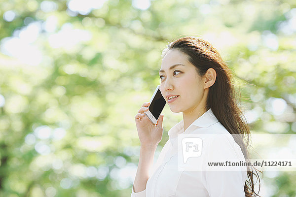 Young Japanese woman on the phone surrounded by green in a city park