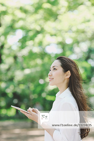 Young Japanese woman with tablet surrounded by green in a city park