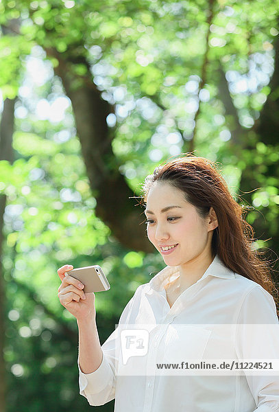 Young Japanese woman with smartphone surrounded by green in a city park