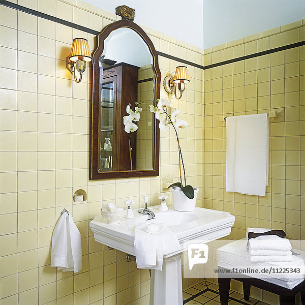 1920s style. Detail of white stately pedestal sink in center and mahogany framed mirror. White orchids sitting on right side of sink. Shade sconces. Cream  yellow wall to wall ceramic tile  dark green or black tiny border on top. Hanging and folded with black ribbon  white cotton linens and towels. White soap bars. Tiny alcove for soap above left side of sink.