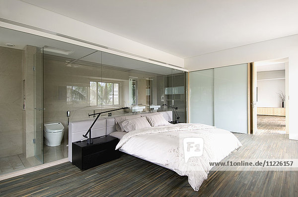 Modern bedroom with glass wall through to bathroom