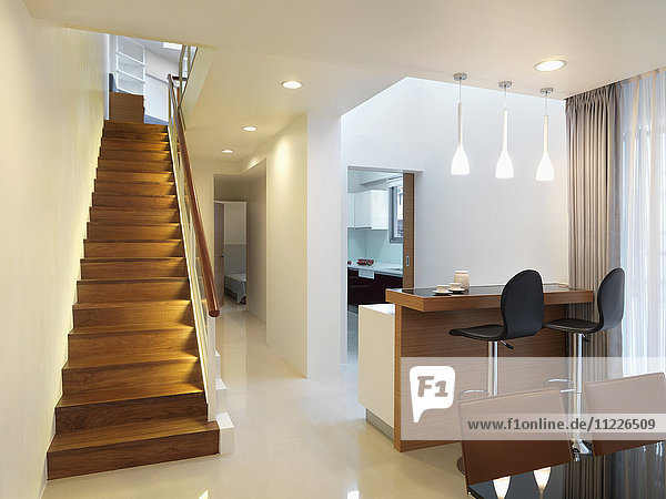 Interior of modern home with straight wooden staircase