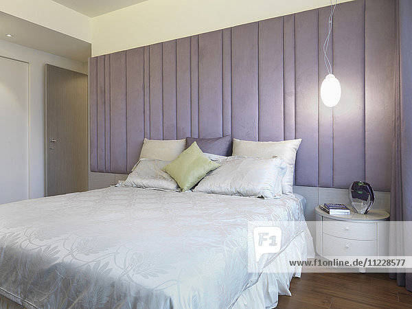 Bed with pillows and purple headboard